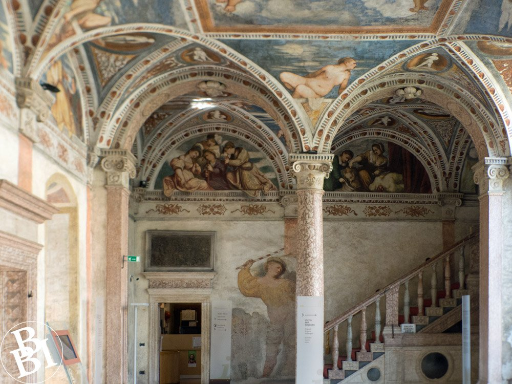 Inside of the castle with archways, a staircase and frescoes