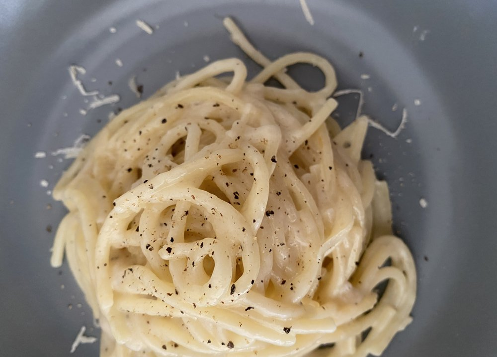 Grey plate with spaghetti and a plain sauce of cheese and pepper