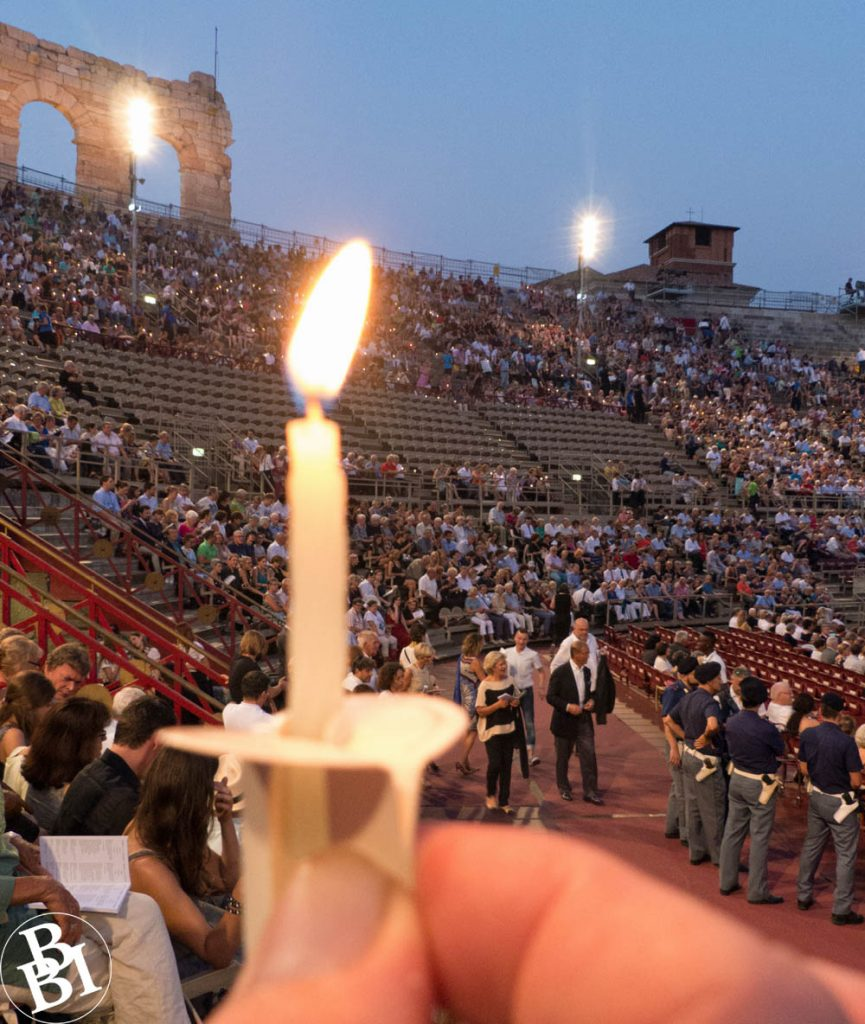 Lighted candle with crowds of people in the distance
