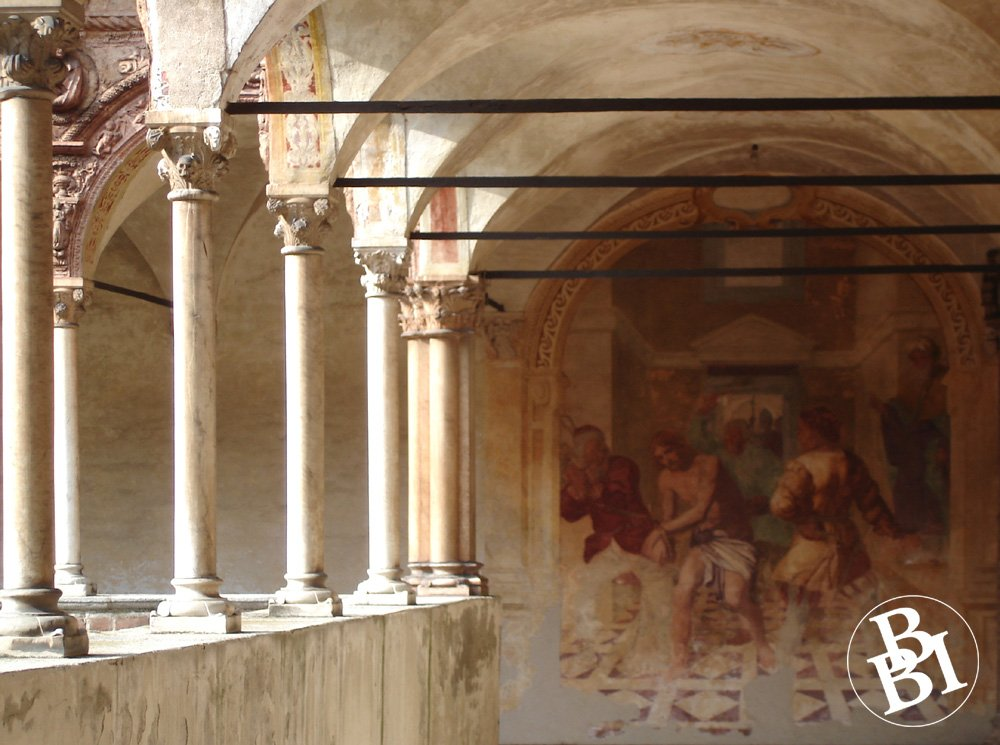 The cloister, with columns and a fresco on the wall