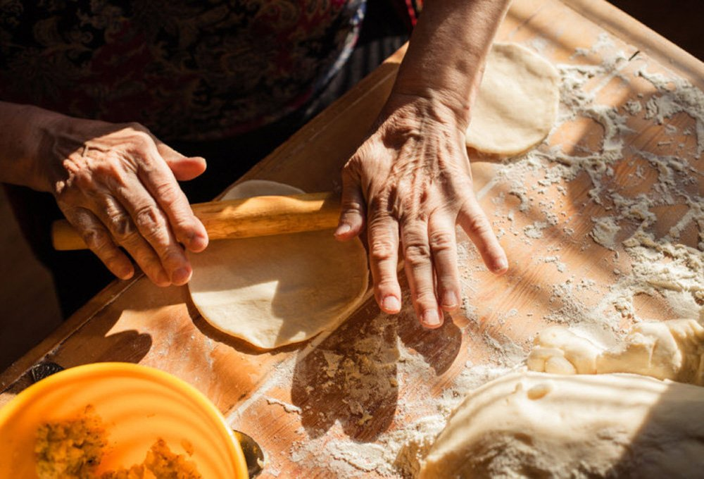 Hands rolling out pasta dough