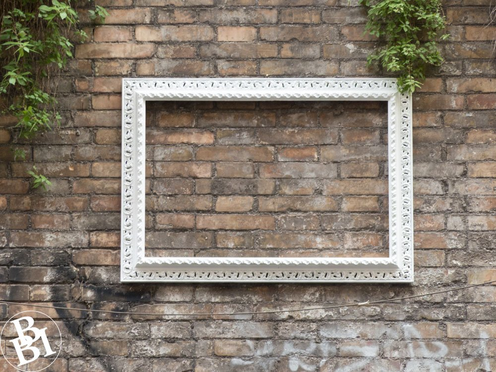 Street art of an empty picture frame fixed to a wall