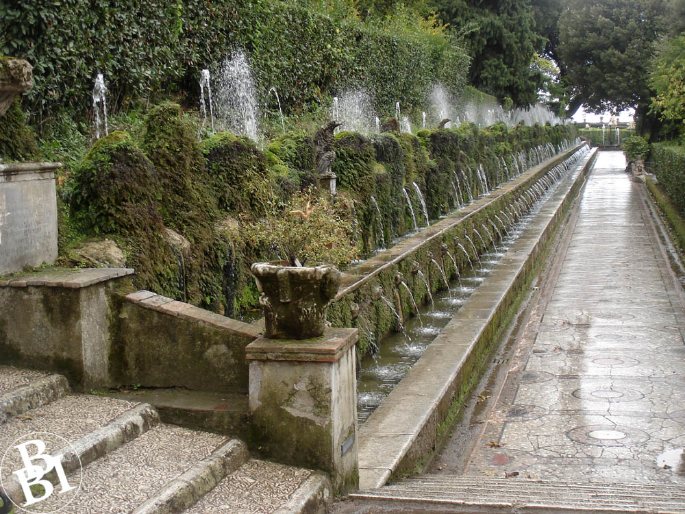 Long row of fountains and trees beside a path