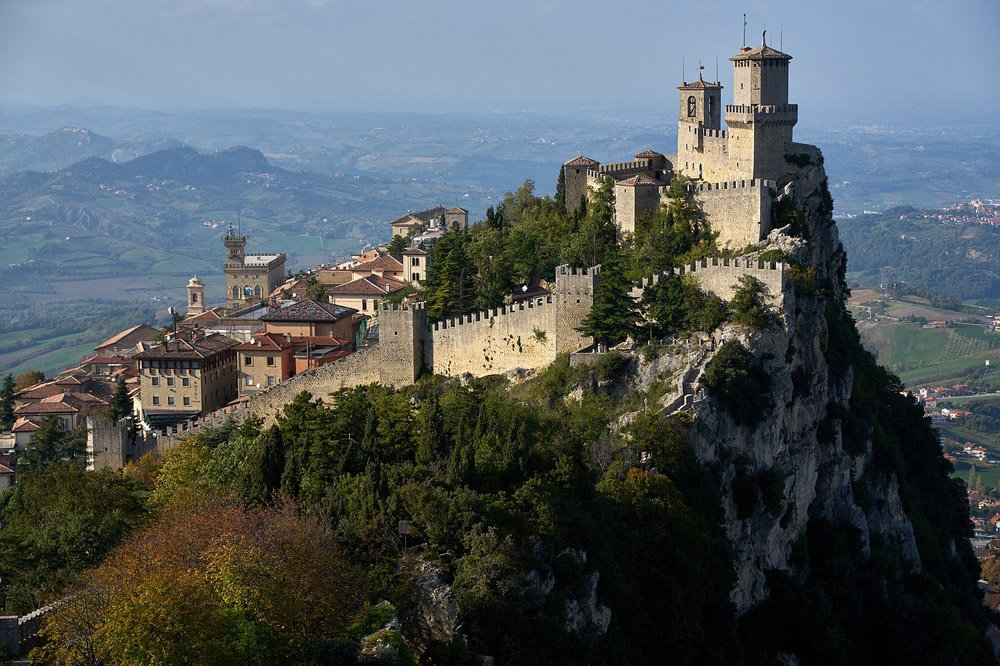 Fortress surrounded by trees on top of a tall mountain