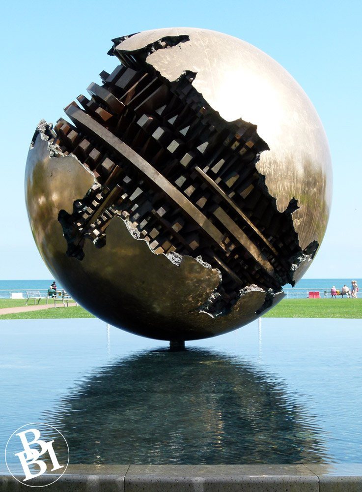 Sculpture of a bronze sphere sitting on the water