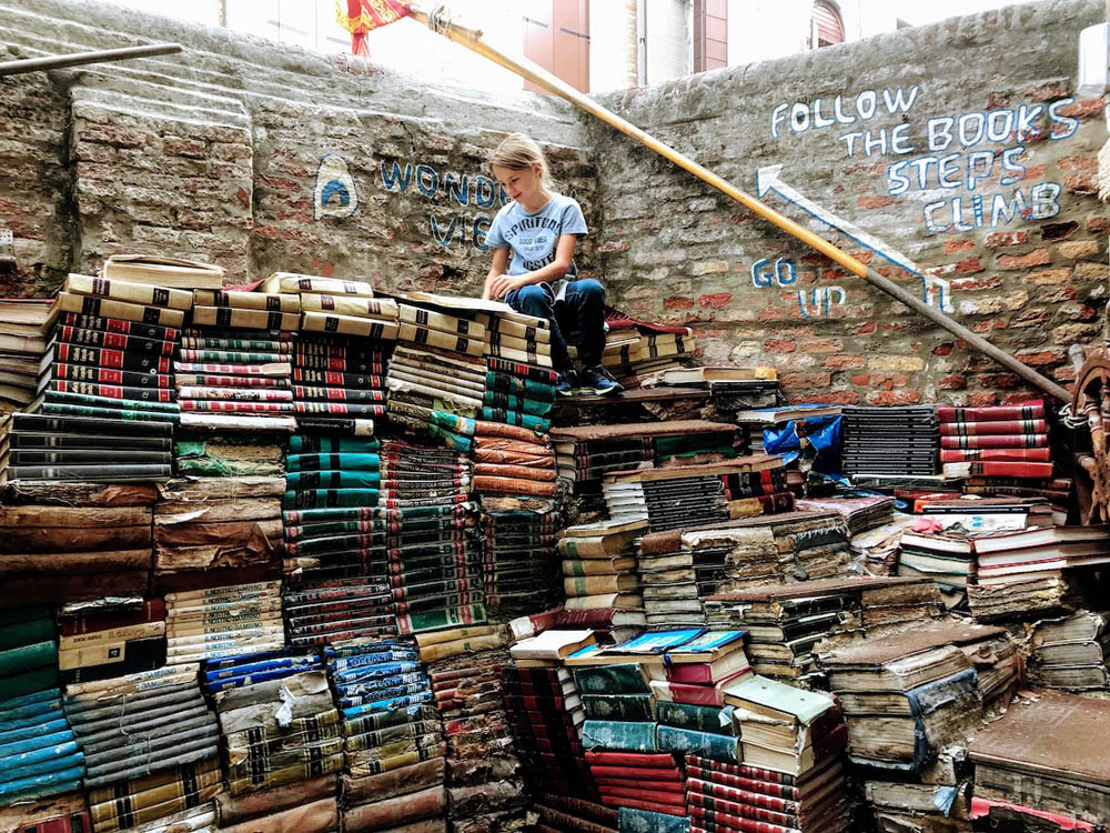 person sitting on top of a big pile of books
