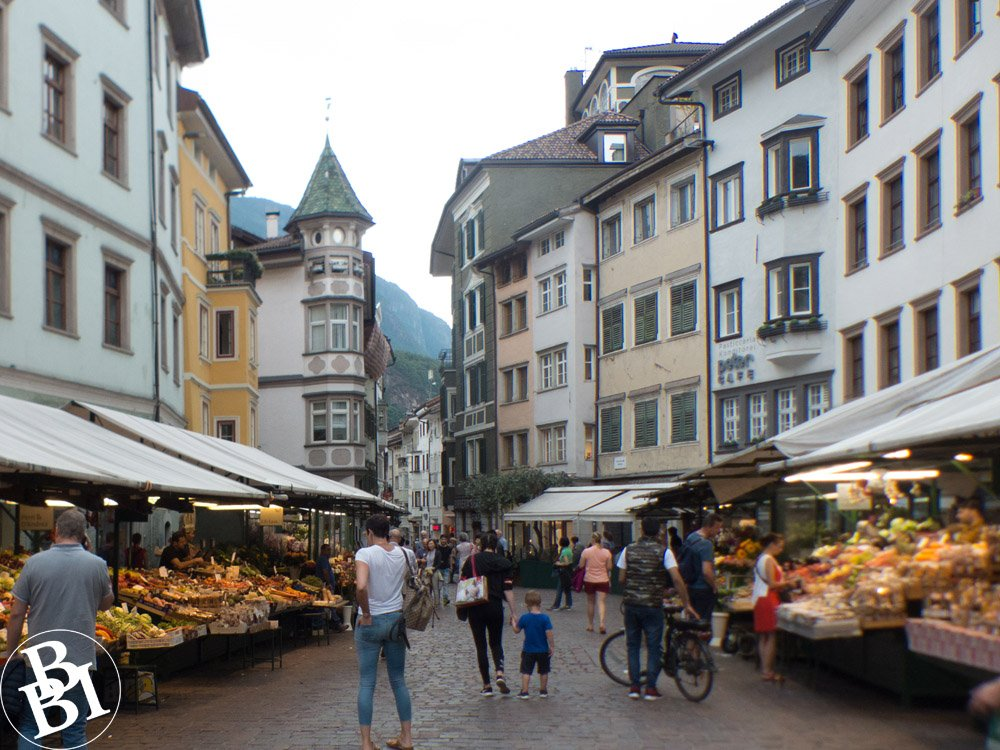 Old street with market stalls piled up with fruit and vegetables