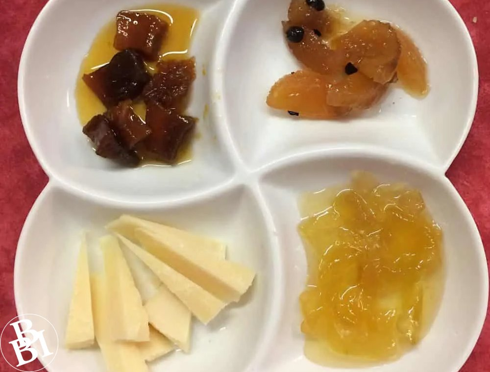 White dish with mostarda di Mantova including cheese and fruits