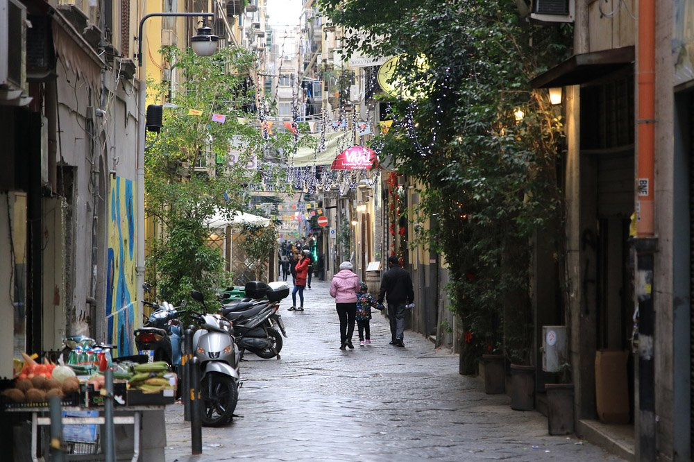 Narrow street with tall buildings, trees, shoppers and motorbikes