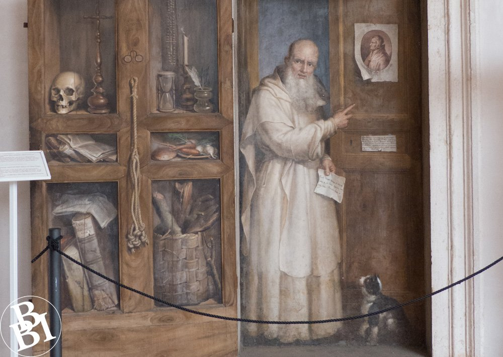 Painting of an ornate doorway and a monk looking out