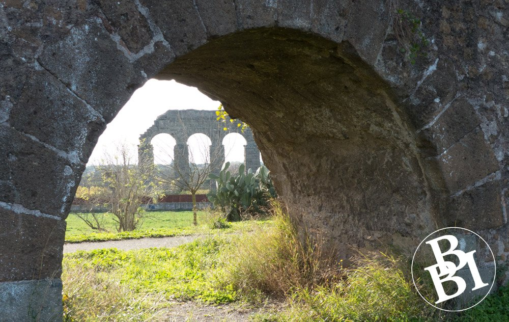 Looking through an arch to a Roman aqueduct