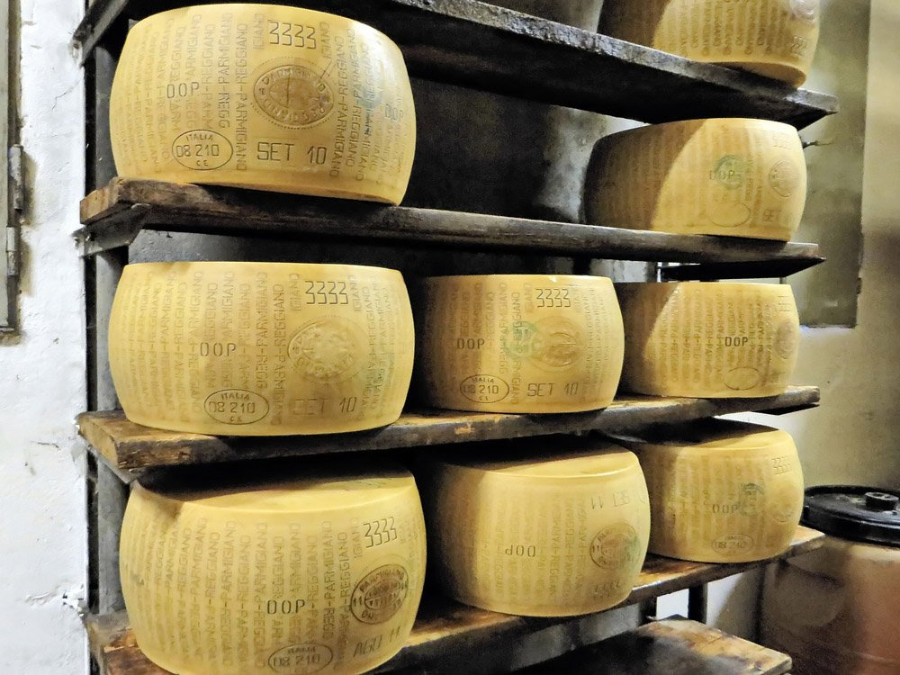Round parmesan cheeses stacked on shelves
