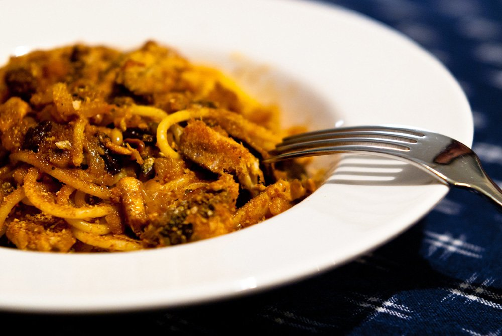 White plate with a fork digging into a dish of pasta and sardines