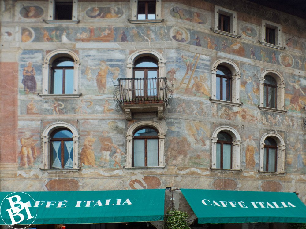 Outside of a building with frescoes and green canopies above a restaurant