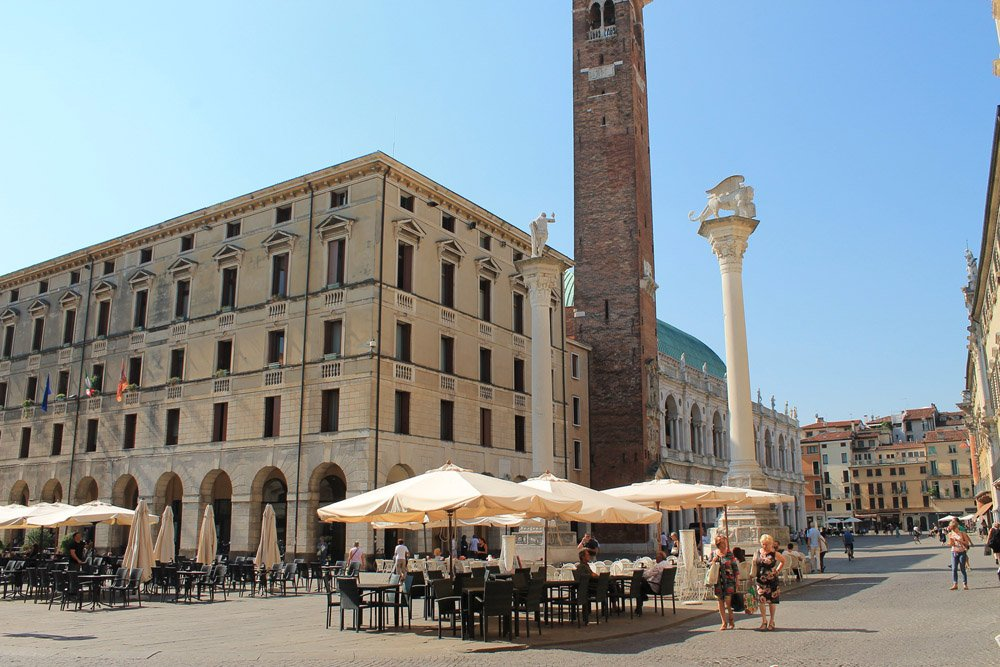 Large square with grand buildings, tall bell tower and restaurant tables