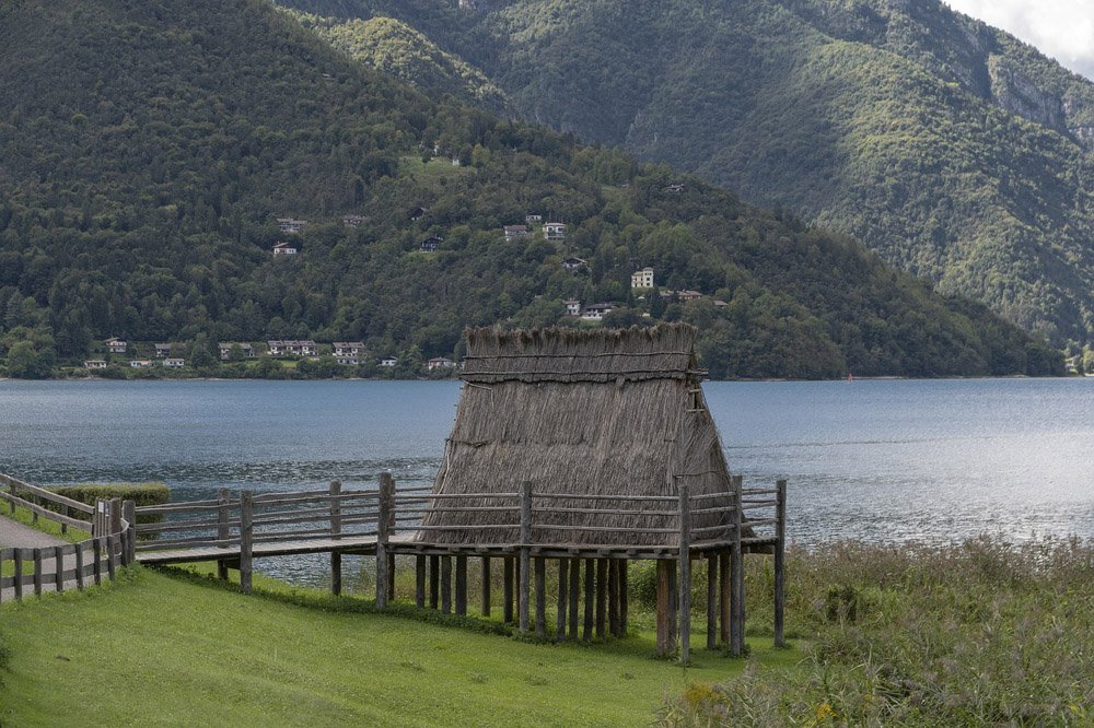 Remains of a prehistoric house on stilts beside a lake with mountains behind