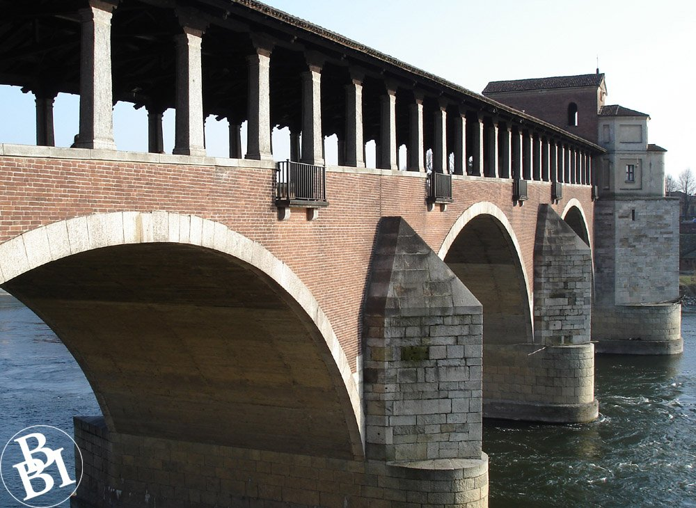 Red brick bridge topped with pillars and a roof