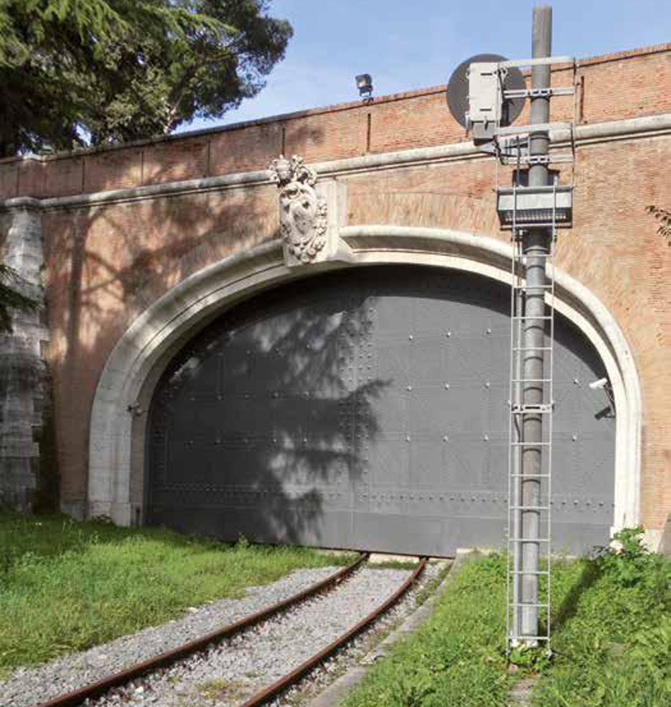 Railway line leading into a closed gateway in a wall
