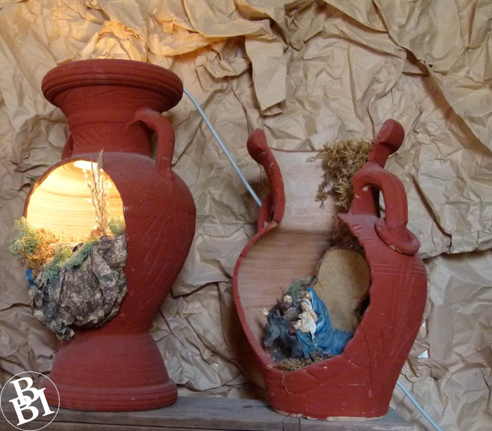 Two brown jugs with sides broken to show nativity scenes inside