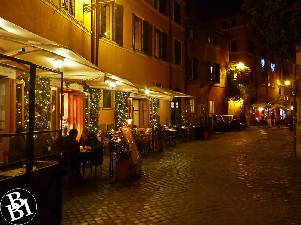 Night time street with people sitting outside restaurants
