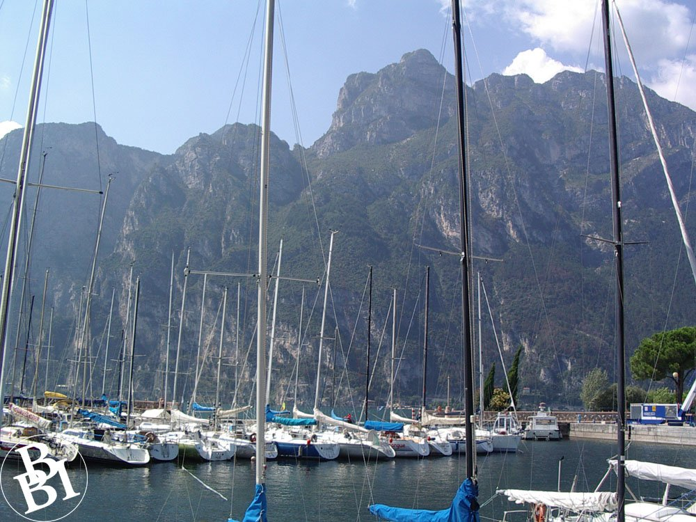 Boats with tall masts in the lake and a backdrop of high mountains