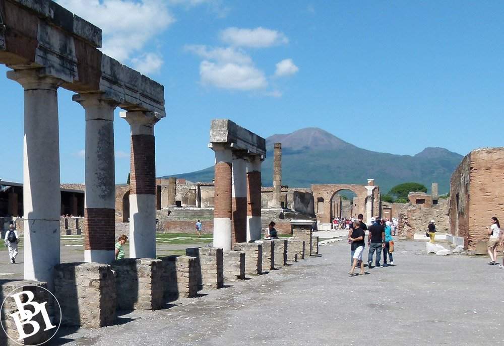 Ruins of Roman columns and arches with Mount Vesuvius in the background
