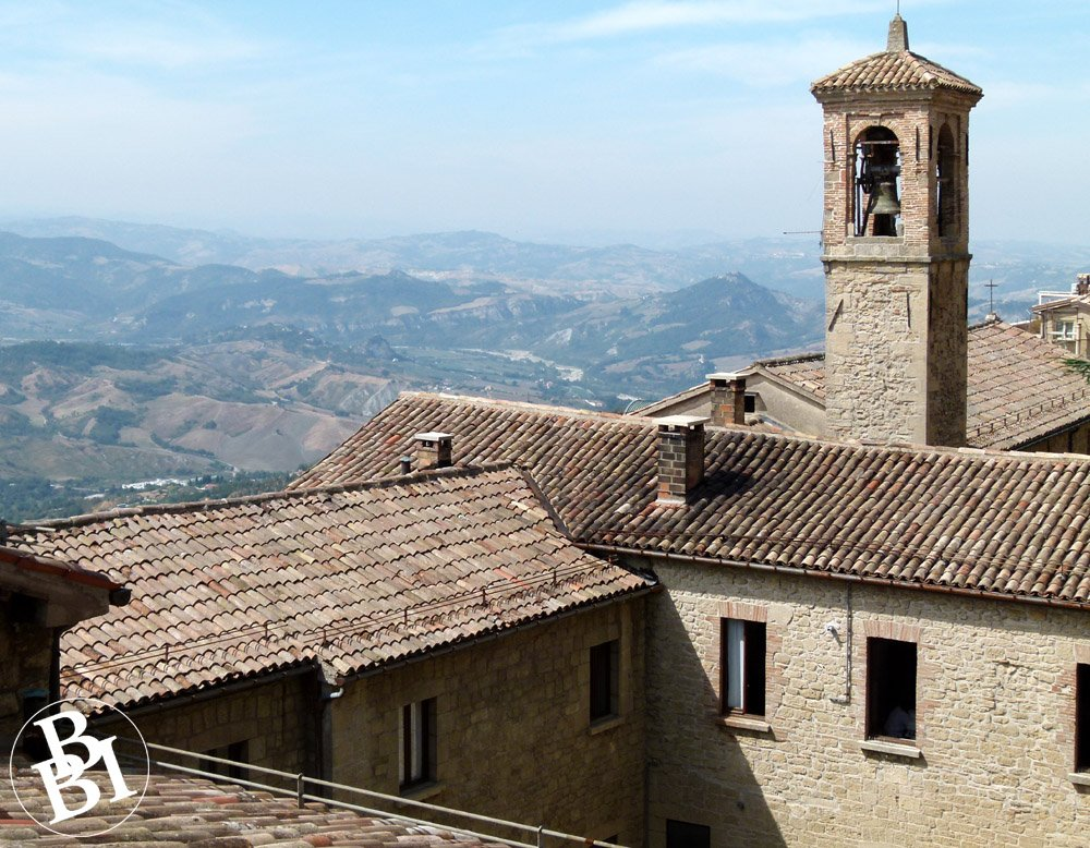 Rooftops and a tower with mountains in the distance