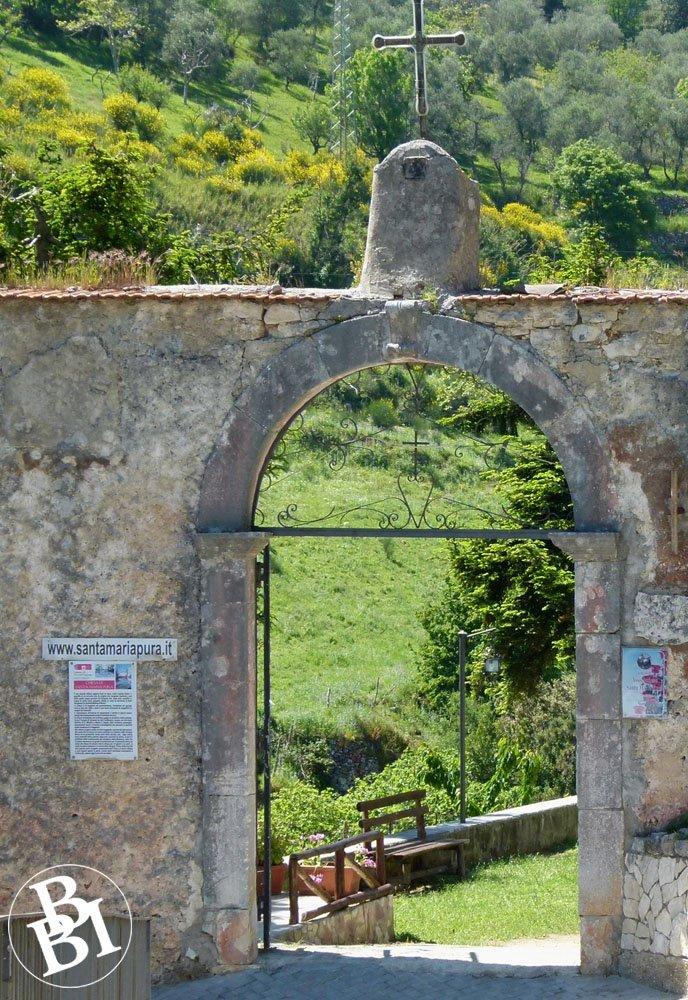 Looking through an archway to hillside churchyard