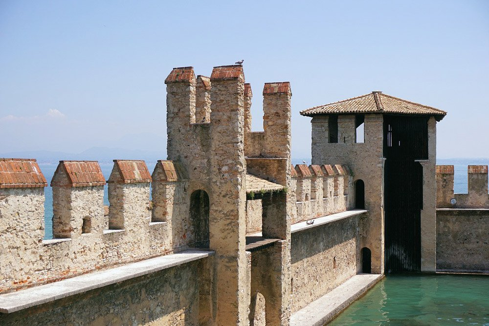 Water surrounded by castle walls with battlements and a tower