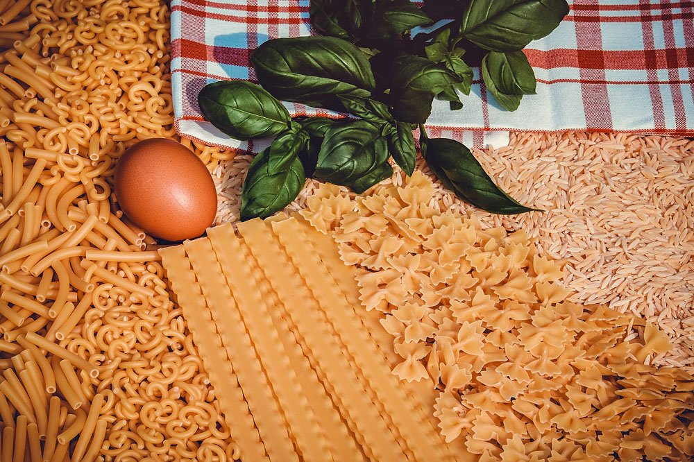 Different pasta shapes, with an egg and a bunch of basil