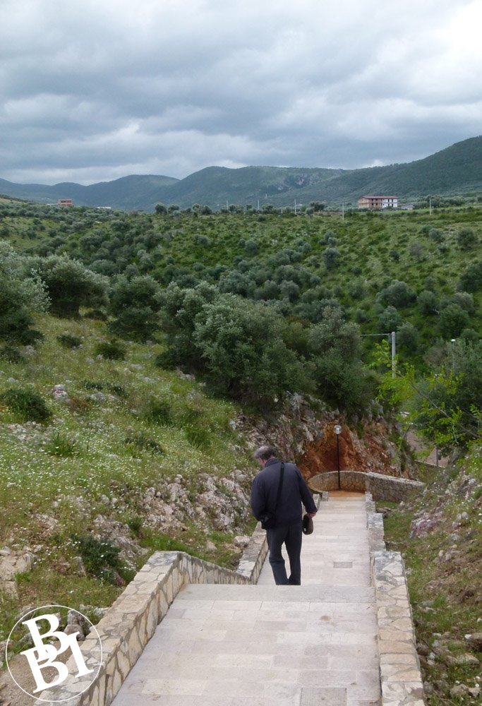 Man walking down steps with view of the valley in distance