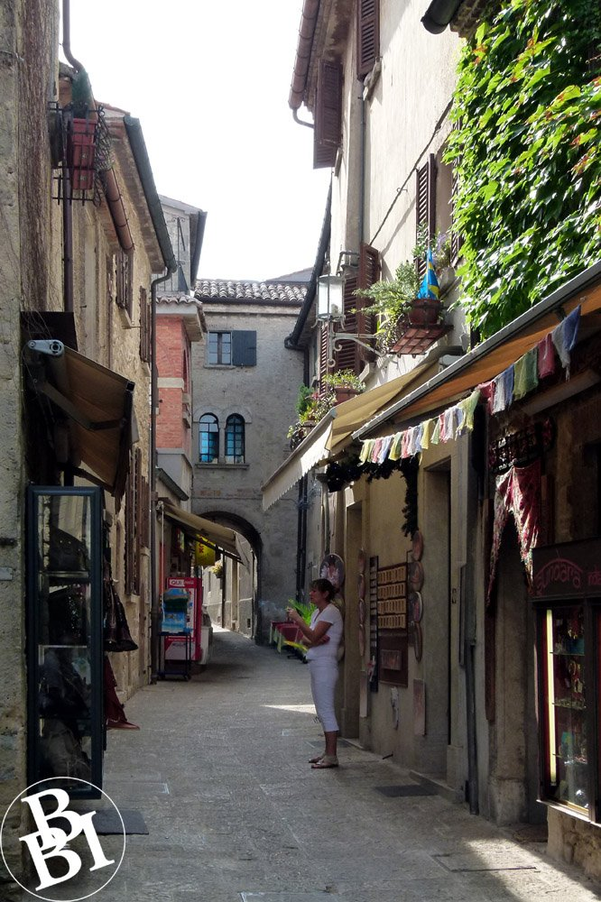Narrow street with shops and an archway at the end