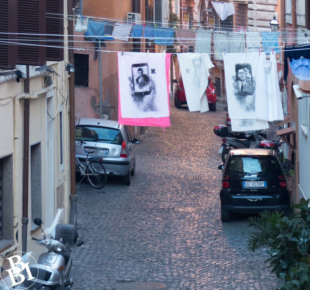 Back street with cars and a motorbike and washing hanging between the houses