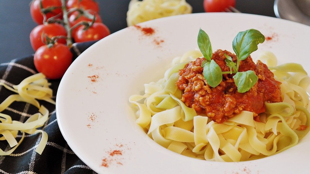 White plate with tagliatelle and bolognese sauce, one of the most famous Italian pasta dishes