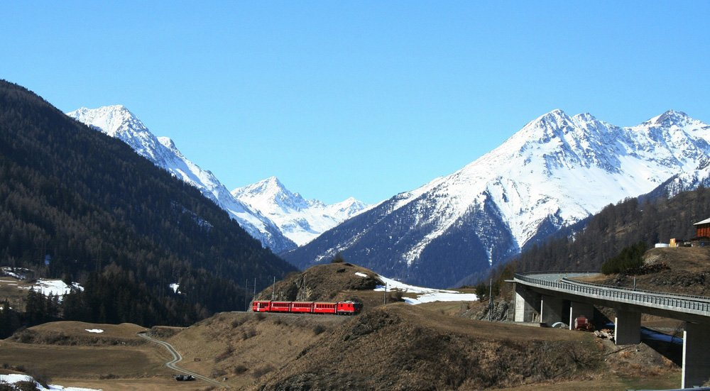 Red train passing through a valley beneath tall ice capped mountains