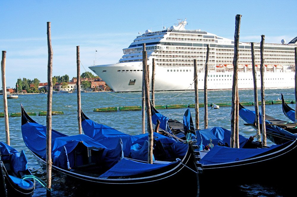 Venice lagoon with blue gondolas and a large cruise ship