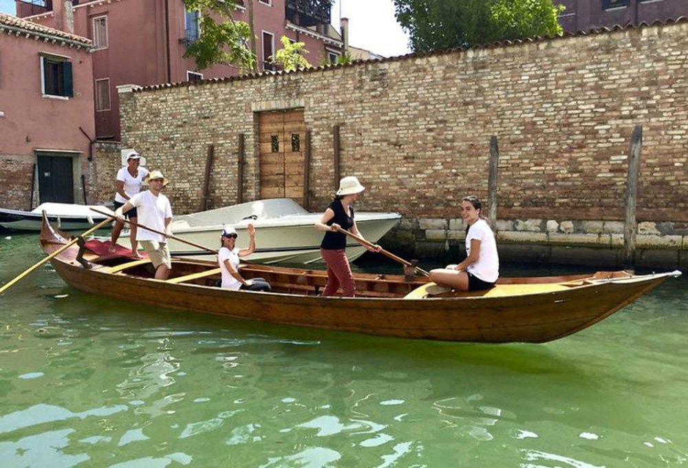 Tourists learning to row a gondola