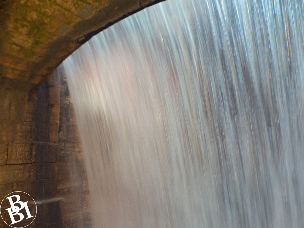 A solid sheet of water, seen from behind the waterfall