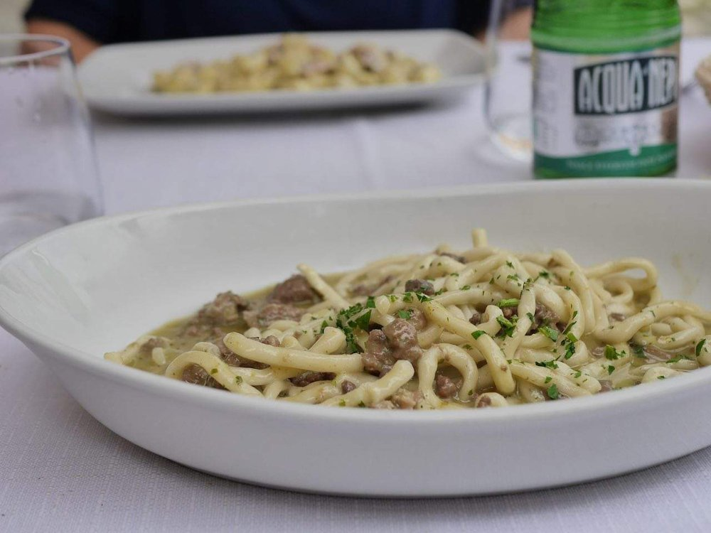 White dish of homemade pasta on a table with a green water bottle